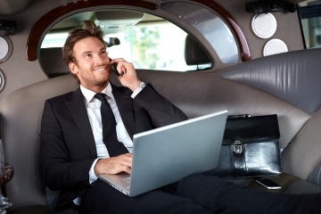 Smiling handsome businessman sitting in luxury limousine, working on laptop computer, smiling.